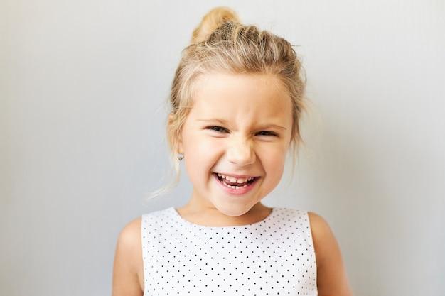 Gioia, emozioni positive e concetto di infanzia felice. bella adorabile bambina che esclama eccitata, felicissima perché sta andando al parco di divertimenti, al cinema o a fare shopping, ridendo ad alta voce Foto Gratuite