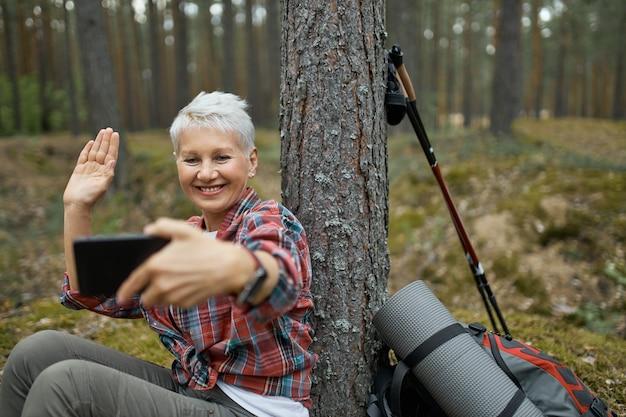 Радостная активная пенсионерка сидит под деревом с походным снаряжением, держит сотовый телефон, улыбается и машет рукой, разговаривает со своим другом по видеоконференции с помощью онлайн-приложения. Бесплатные Фотографии