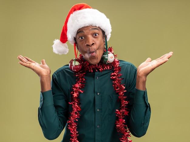Gioioso uomo afroamericano in santa cappello con ghirlanda e palle di natale sulle orecchie divertendosi guardando la telecamera in piedi su sfondo verde Foto Gratuite