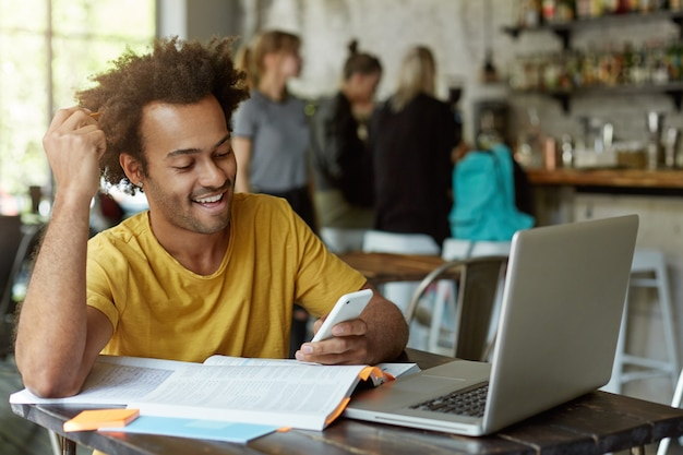 Joyful african american student sitting at wooden table in cafe surrounded with books, exercise books, laptop holding cell phone in hand looking gladly Free Photo
