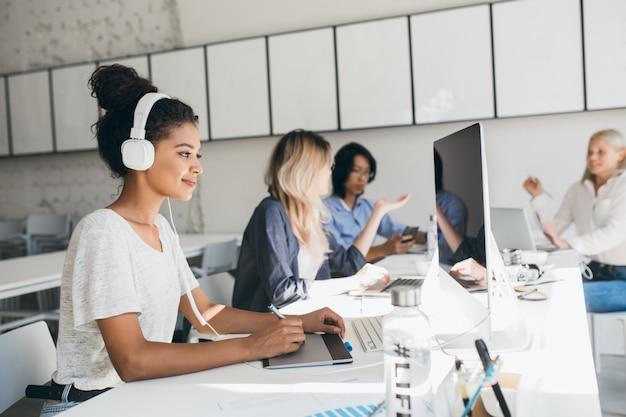 白いヘッドフォンで音楽を聴きながら新しいプロジェクトに取り組んでいる楽しいアフリカのウェブ開発者。話をしている同僚とオフィスで彼女の仕事をしている黒人女性デザイナー。 無料写真