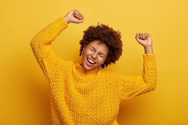 Joyful afro woman raises arms, tilts head, dressed in casual knitted jumper, laughs from happiness, celebrates victory, isolated on yellow Free Photo