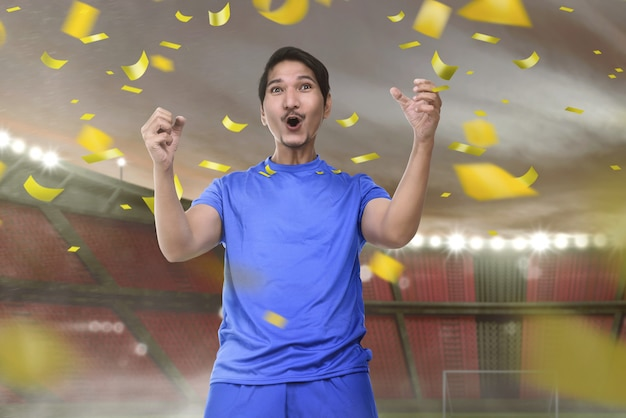 Joyful asian football player man with excited expression Premium Photo