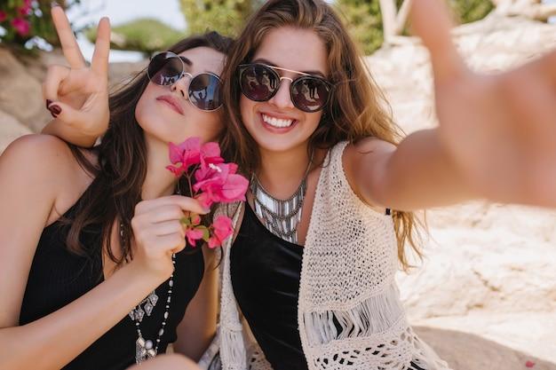 Веселые привлекательные друзья веселятся вместе и делают селфи на летнем курорте. очаровательная девушка в вязаном ретро-наряде расслабляется с сестрой и смеется, проводя время на улице Бесплатные Фотографии