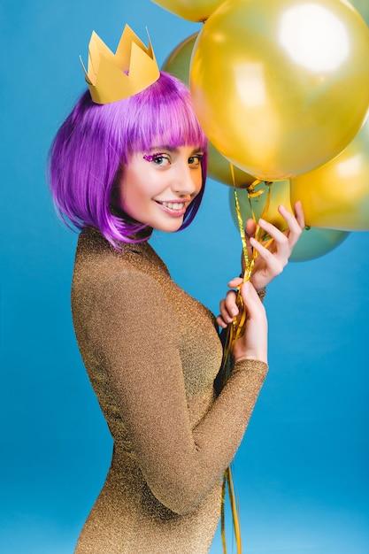Gioiosa attraente giovane donna con i capelli viola tagliati divertendosi con palloncini dorati. corona in testa, trucco con orpelli, vestito alla moda di lusso, festa di capodanno. Foto Gratuite