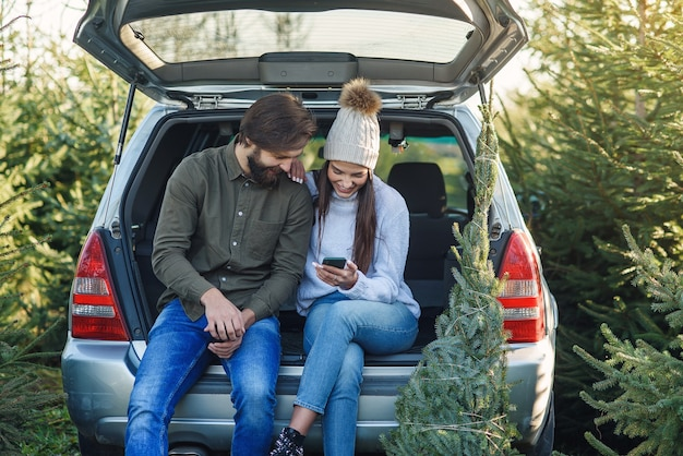 즐거운 수염 난 남자와 예쁜 여자 모자에 전나무 나무를 잡고 사용하는 자동차 트렁크에 앉아 프리미엄 사진