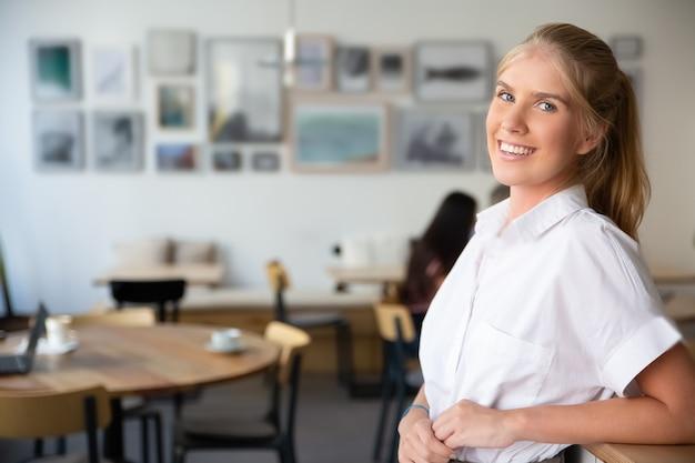 흰색 셔츠를 입고 즐거운 아름다운 금발의 여자, 공동 작업 공간에 서서, 책상에 기대어, 포즈, 무료 사진