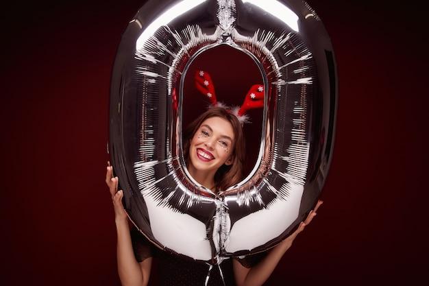 新年会の準備をして、エアナンバーバルーンでポーズをとってイブニングメイクで楽しい美しい若いブルネットの女性 無料写真