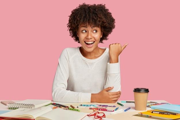 Gioiosa signora creativa nera ha un'espressione positiva, punta da parte con il pollice, mostra spazio libero per la pubblicità, posa sul posto di lavoro con taccuino a spirale e pastelli, isolato su muro rosa Foto Gratuite