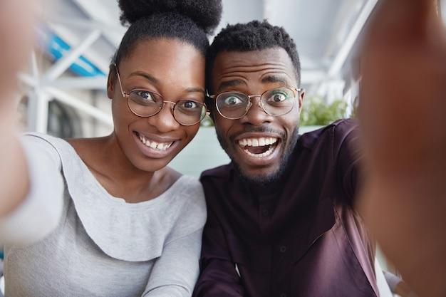 うれしそうな黒人男性と女性の親友は、一緒に楽しんだり、自分の写真を撮ったり、自撮りをするためのポーズをとったり、成功した後は機嫌が良いです。 無料写真
