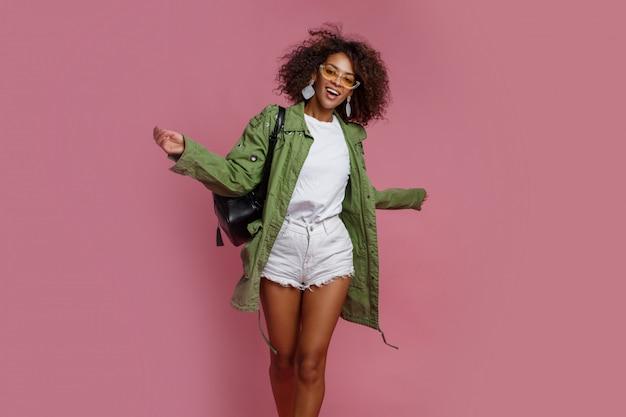 Joyful black woman having fun in studio over pink background. white t-shirt, green jacket. stylish spring look. Free Photo