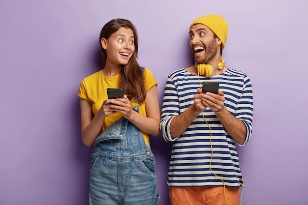 즐거운 남자 친구와 여자 친구가 웃고 서로를 보며 휴대폰을 들고 무료 사진