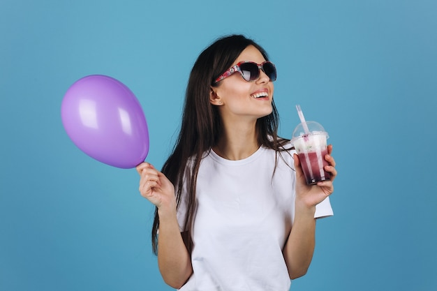 Joyful brunette in black sunglasses looks happy posing with a cocktail and balloon Free Photo