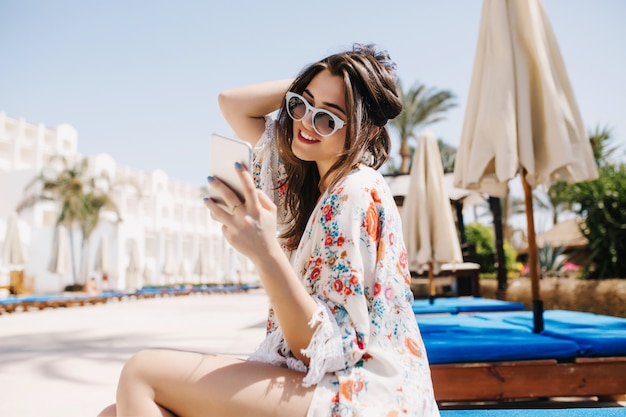 Joyful brunette girl checking mail in social neworks while waiting friends near the hotel to swim in pool together. adorable young woman in sunglasses sitting on chaise-longue and holding white phone Free Photo