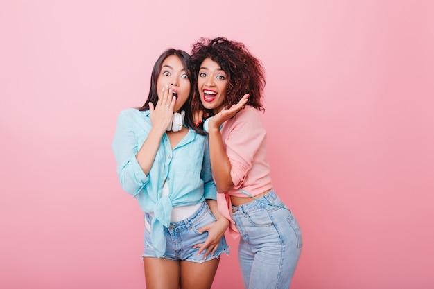 驚きの表情でポーズをとるトレンディなカジュアルな服装でうれしそうなブルネットの女の子。ピンクの部屋に立っている黒髪の愛らしい若い女性の屋内写真。 無料写真