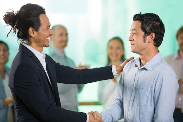 Joyful Businessmen Shaking Hands after Meeting Free Photo