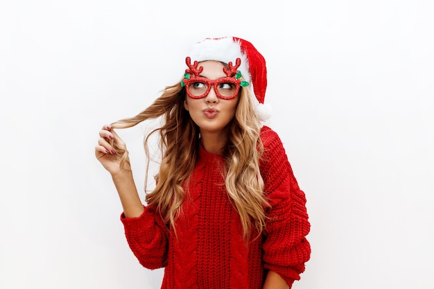 Gioiosa donna bionda spensierata in simpatici occhiali mascherati e cappello di capodanno in maglione lavorato a maglia rosso in posa sul muro bianco. isolato. natale e nuovo concetto di festa di prova. Foto Gratuite
