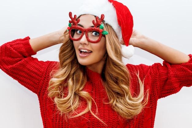 Gioiosa donna bionda spensierata in occhiali da travestimento carino e cappello di capodanno in maglione rosso in posa Foto Gratuite