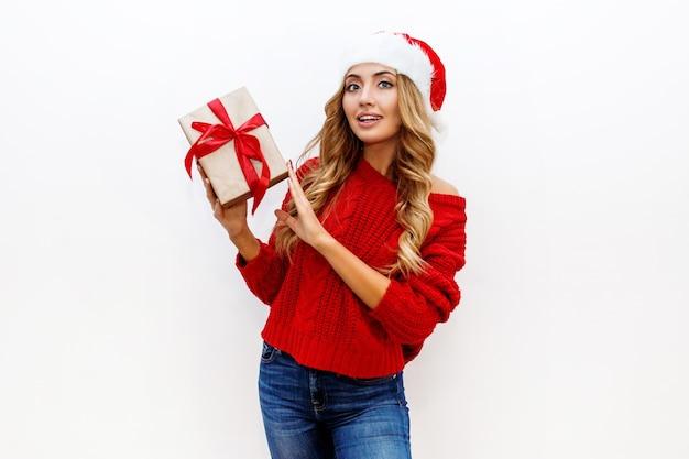 귀여운 가장 무도회 안경과 흰 벽에 포즈 빨간 니트 스웨터에 새 해 모자에 즐거운 평온한 금발 여자. 격리. 크리스마스와 새 해 파티 개념. 무료 사진