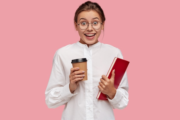 Радостная кавказская молодая девушка в белой одежде держит ароматный кофе на вынос и книгу Бесплатные Фотографии