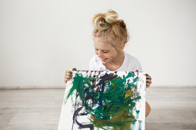 Gioiosa, allegra, sorridente con i denti e guardando la sua foto piccola bionda. maglietta bianca d'uso della bambina europea che si siede sul pavimento e che tiene immagine. Foto Gratuite