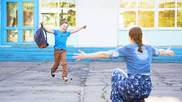 Joyful child runs into the arms of his mother. Premium Photo