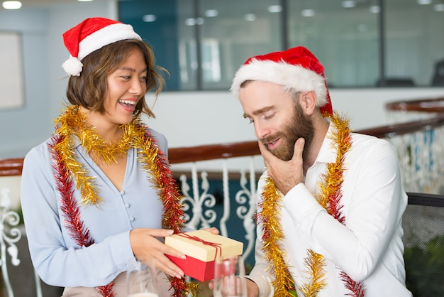 Joyful colleagues in christmas hats exchanging gifts Free Photo
