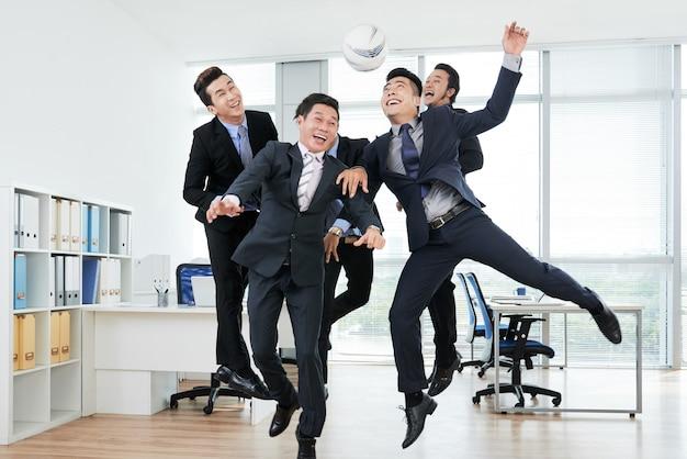 Joyful colleagues playing keepie-uppie Free Photo