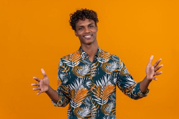 Радостный, уверенный в себе симпатичный темнокожий мужчина с вьющимися волосами в рубашке с принтом листьев, раскрывающей руки для объятий на оранжевом фоне Бесплатные Фотографии