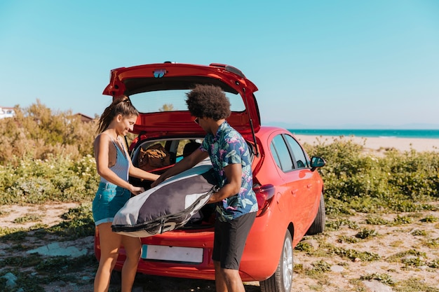 Joyful couple getting things out of trunk on beach Free Photo