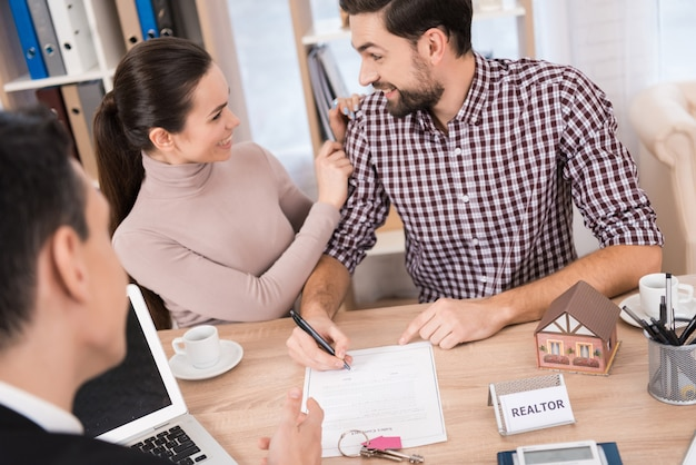 Joyful couple signs contract for purchase of new house Premium Photo