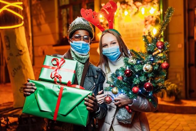 Радостная пара стоит вечером в городе с рождественскими подарками в медицинских масках Premium Фотографии