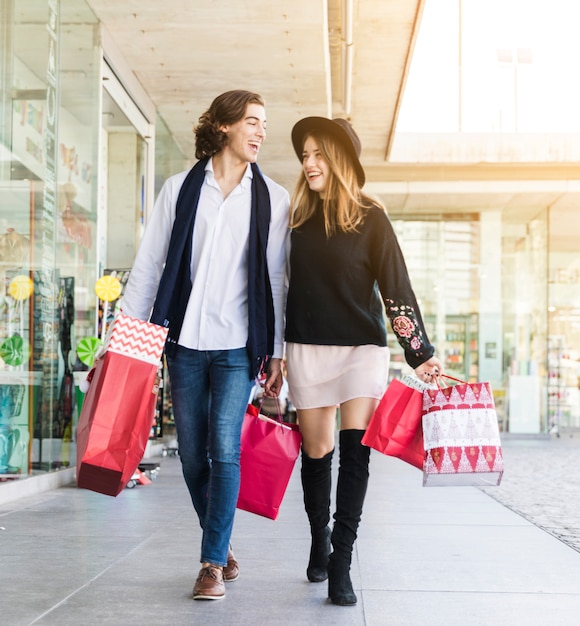 Joyful couple walking with shopping bags Free Photo