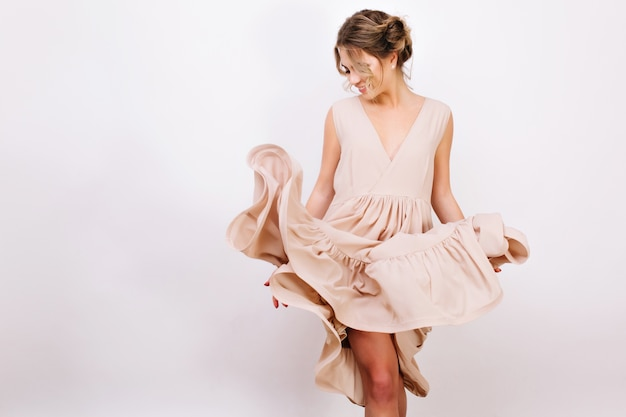 Радостная кудрявая девушка с милой прической игриво позирует, примеряя новое стильное платье. стройная молодая женщина в модной винтажной одежде, танцы, изолированные на белом фоне. Бесплатные Фотографии