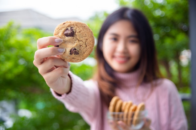 Joyful cute teenage holding cookie at home Free Photo