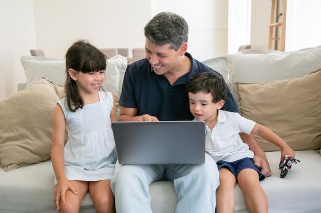 うれしそうなお父さんが画面を指して、ラップトップのコンテンツを幸せな子供たちに見せています。 無料写真