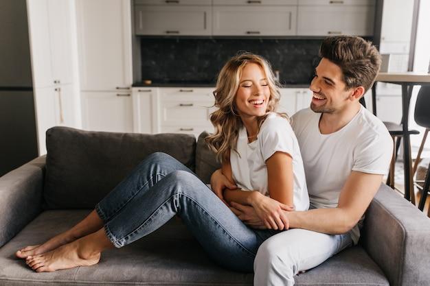 Радостного дня вместе в уютных и теплых квартирах. счастливый привлекательный парень с красивой девушкой, глядя друг на друга, смеясь и обнимаясь на диване. Бесплатные Фотографии