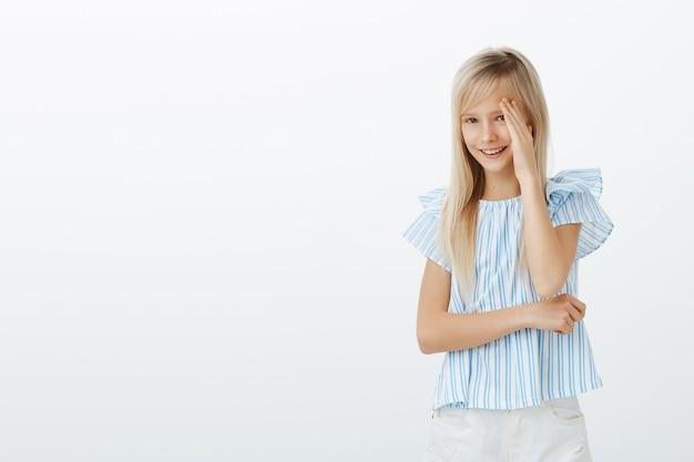 長いブロンドの髪を持つうれしそうな恥ずかしいかわいい女の子、片側から顔を手のひらで覆い、広い笑顔、父が新しい衣装で彼女の写真を撮っている間、ぎこちない感じ 無料写真