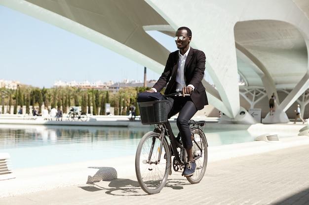 黒いフォーマルスーツとスタイリッシュな色合いを身に着けている、環境に配慮したアフリカのサラリーマン。 無料写真
