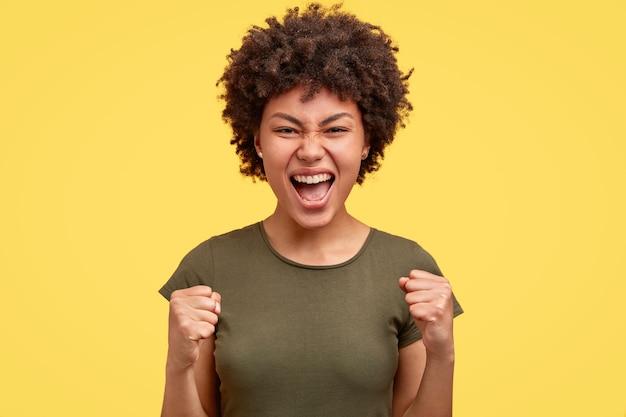 アフロの髪型、勝利で拳を握り締める、うれしそうな民族の若い女性は、素晴らしい成果を上げました 無料写真