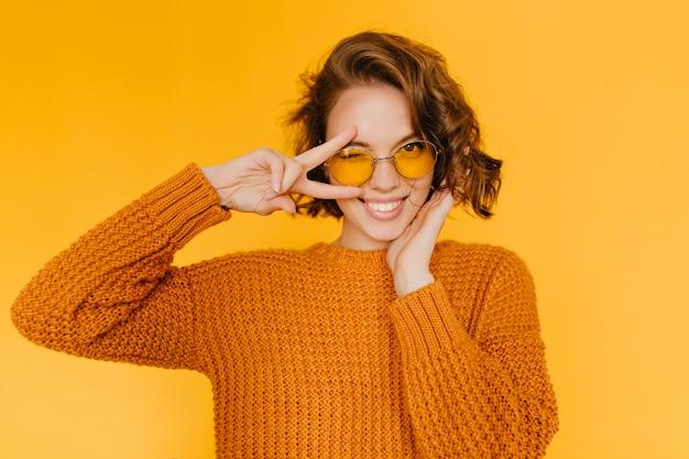 Gioiosa donna europea con riccioli lucidi ridendo e mostrando il segno di pace su sfondo giallo Foto Gratuite