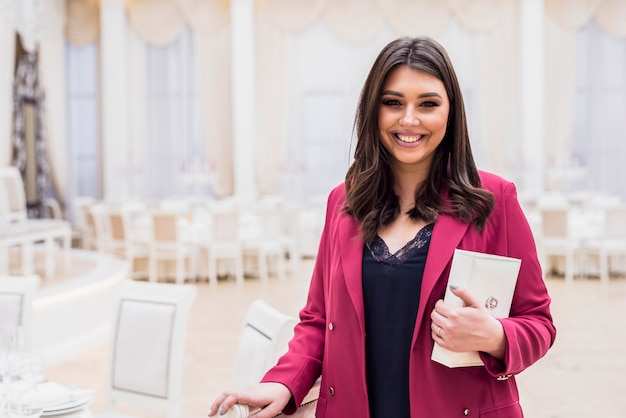 Joyful event manager in banquet hall Free Photo