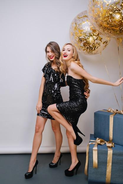 즐거운 국방과 여자 재미 파란색 선물 상자 옆에 춤과 미소로 찾고. 생일 파티 중에 함께 시간을 보내는 두 사랑스러운 여자의 실내 초상화. 무료 사진