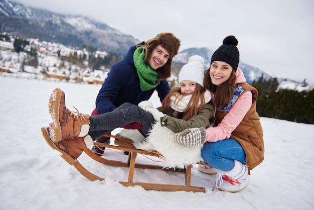 Радостная семья, наслаждающаяся катанием на санках на холме Бесплатные Фотографии