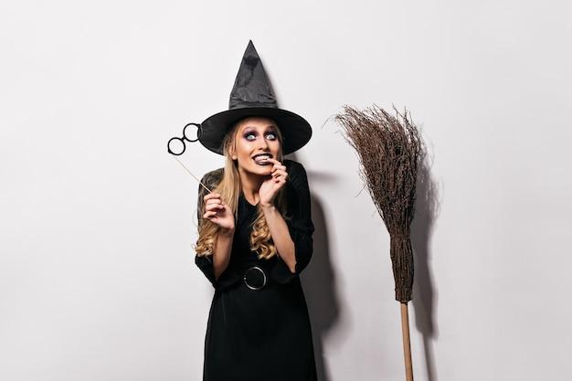 Радостная женская модель с темным макияжем готовится к карнавалу. девушка jocund в костюме хэллоуина корчит рожи. Бесплатные Фотографии