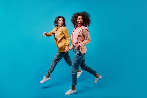 Радостные женские модели, работающие на синей стене Бесплатные Фотографии