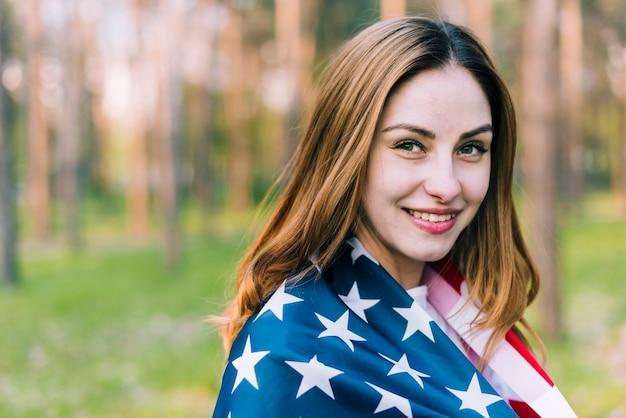 Joyful female wearing usa flag on shoulders Free Photo