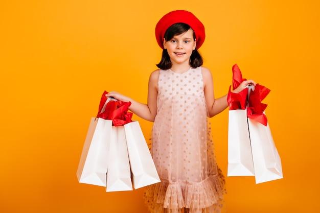 買い物の後にポーズをとるうれしそうなフランスの子供。紙袋で笑顔の子供。 無料写真