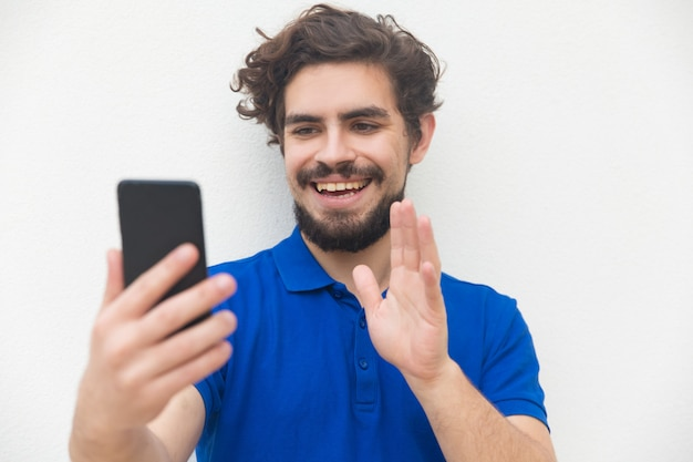 Joyful friendly guy with smartphone waving hello Free Photo