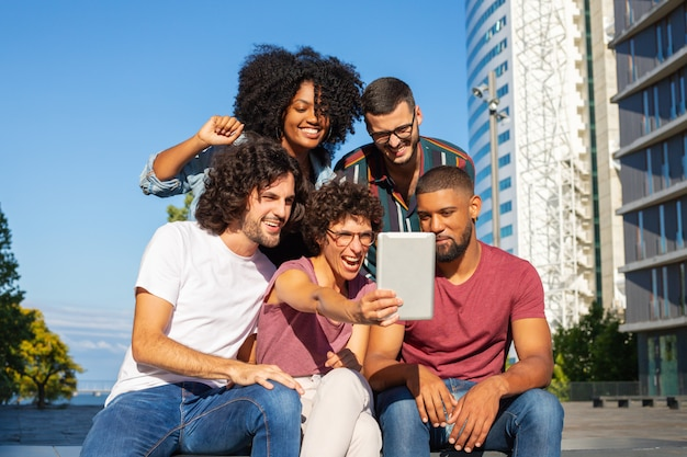 Joyful friends using tablet for group video call Free Photo